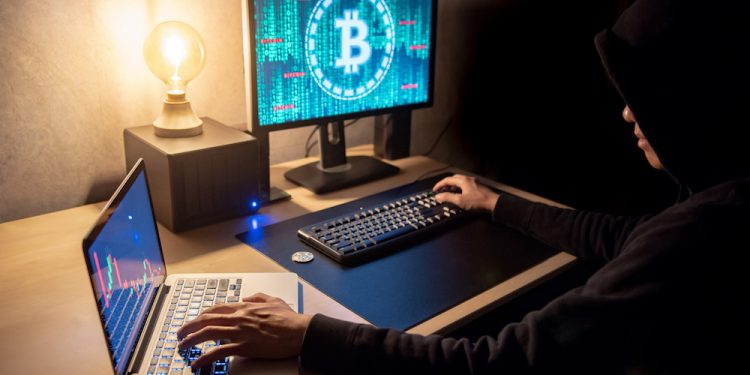 Hacker man using laptop and computer with Bitcoin green binary graphic and cryptocurrency candlestick graph price on monitor screen. Cyber crime digital currency laundering concept